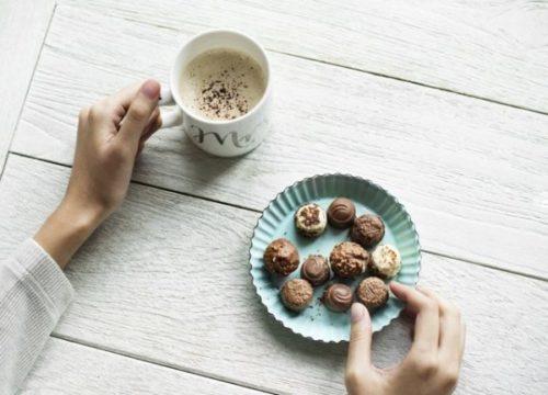 コーヒーを飲みながらチョコレートをつまもうとしている女性の手元の画像