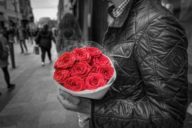 バラの花束を抱えて恋人を待つ男性の画像