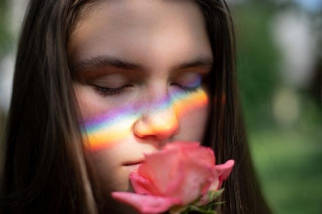 花の匂いを嗅ぐ女性の画像