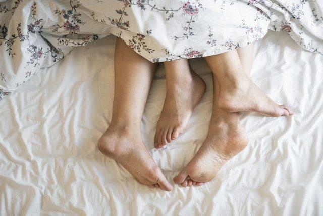 ベッドでの男女の脚の画像