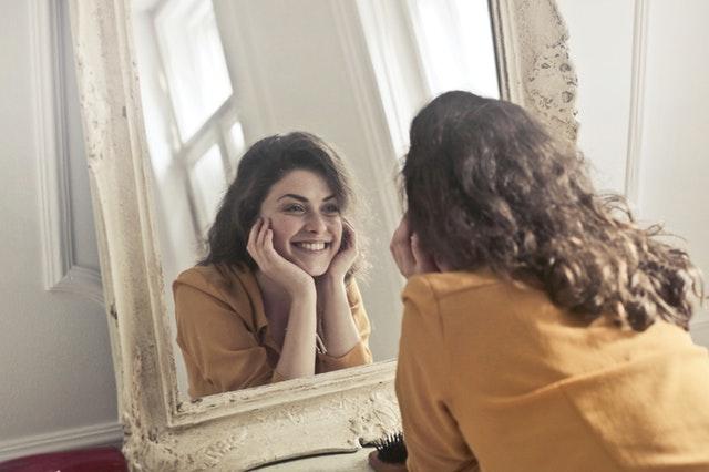 鏡の前でほほ笑む女性の画像