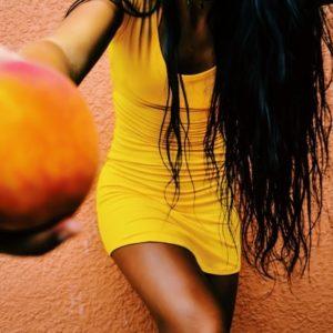 桃を手にする女性の画像