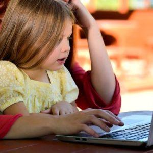 子どもが母親とパソコンに向かう画像
