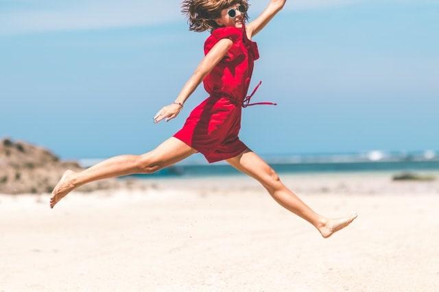 浜辺で飛び跳ねる女性