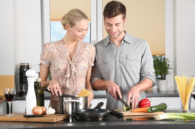 キッチンに立つカップルの画像