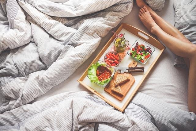 ベッドで朝食を摂る女性
